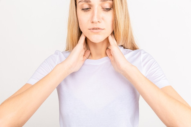 Female checking thyroid gland by herself. close up of woman in white t- shirt touching neck with red spot