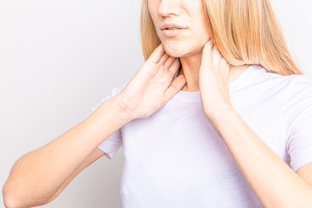 Female checking thyroid gland by herself. close up of woman in white t- shirt touching neck with red spot.