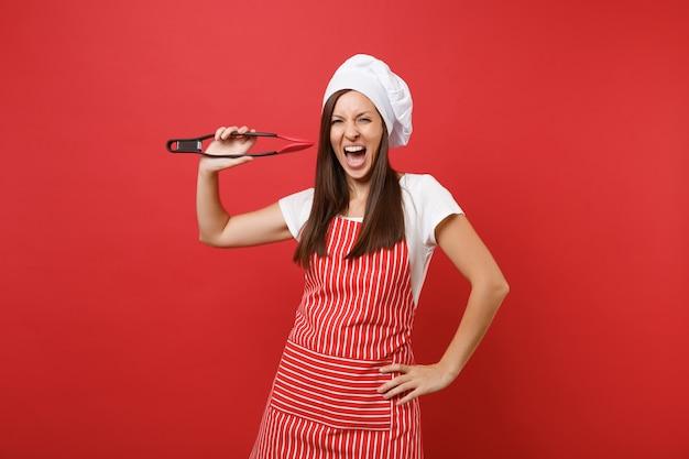 Повар женского пола или пекарь в полосатом фартуке, белой футболке шляпе шеф-повара toque изолированной на красной предпосылке стены. женщина держит кухонный салат, обслуживающий пластиковые щипцы для гриля. копируйте концепцию пространства копии.