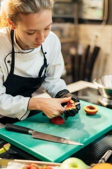 Женщина-повар режет фрукты на кухне