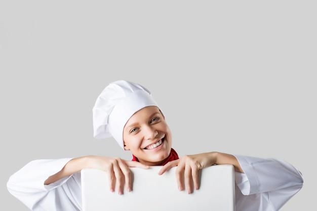 テキストのポスターを保持している女性シェフ、ポスターを見て、白い背景に笑顔