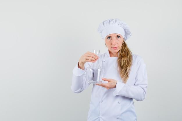 Женщина-повар держит химическую колбу в белой форме