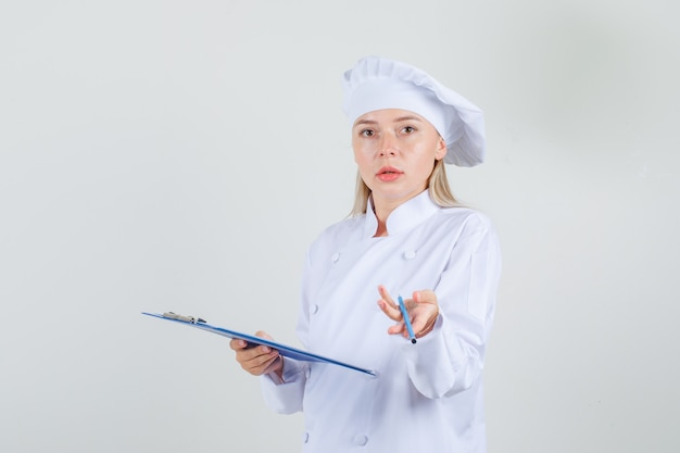 Cuoco unico femminile che tiene appunti con la matita in uniforme bianca e che sembra confuso