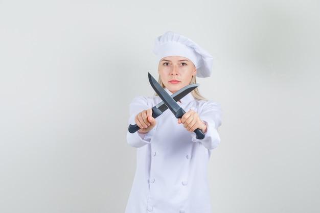 Cuoco unico femminile che tiene i coltelli dell'incrocio in uniforme bianca e che sembra serio