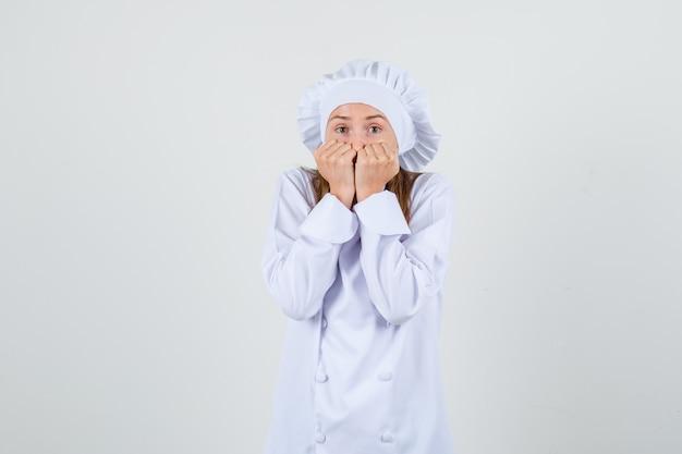白い制服を着た女性シェフが拳を口に抱えて怖がっています。正面図。