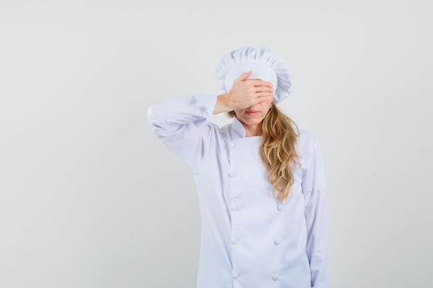 Cuoco unico femminile che tiene la mano sugli occhi in uniforme bianca e che sembra spaventato