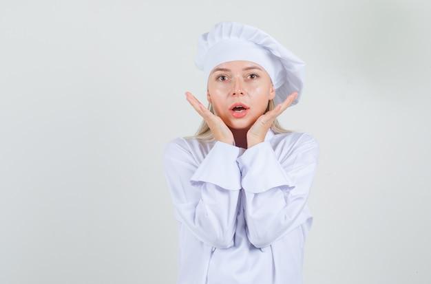 Cuoco unico femminile che tiene le mani vicino alle guance in uniforme bianca e che sembra spaventato