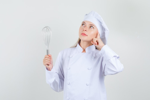 Female chef holding whisk and looking up dreamily in white uniform