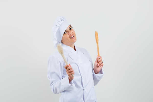 白い制服を着た木のスプーンとフォークを持って自信を持って見える女性シェフ。
