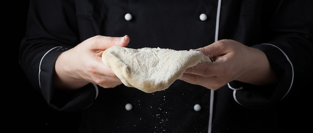 Female chef holding yeast dough.