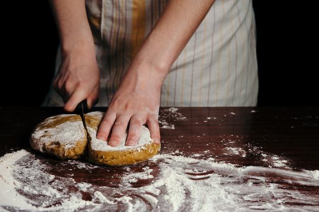 Женщина-повар в фартуке режет тесто на деревянном столе с мукой