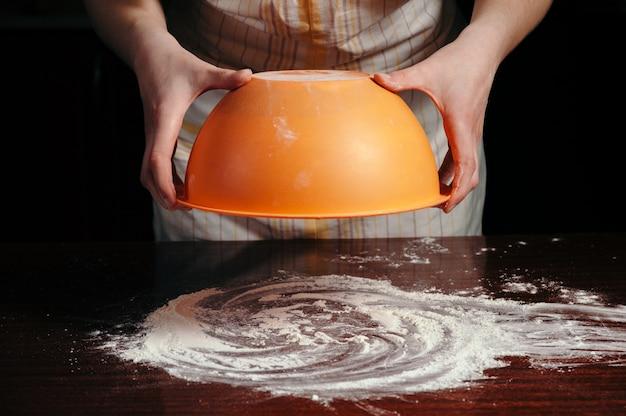 Женщина-повар в фартуке держит миску с застрявшим тестом вверх дном над деревянным столом с мукой
