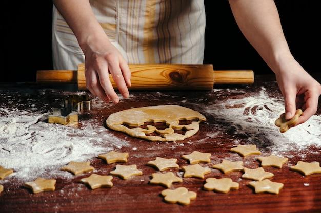 Повар в фартуке делает печенье в форме звезд из теста на деревянном столе с мукой