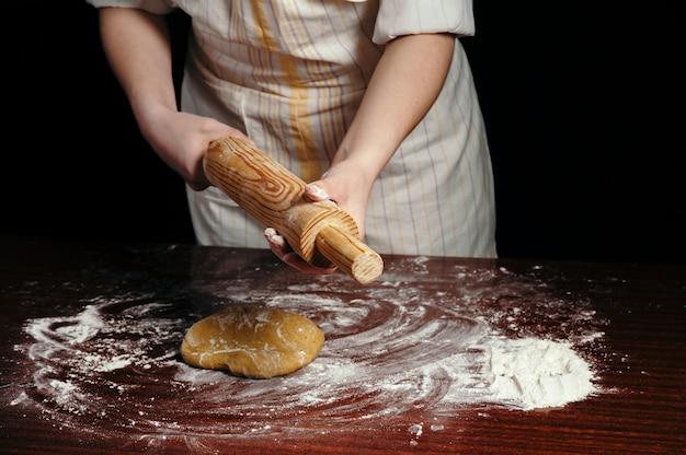 Женщина-повар в фартуке со скалкой и тестом на деревянном столе с мукой
