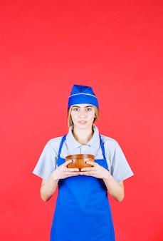 Шеф-повар в синем фартуке держит чашку китайской медной лапши