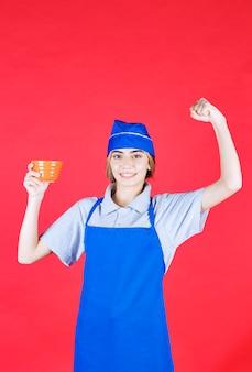 파란색 앞치마를 입은 여성 요리사가 국수 컵을 들고 주먹을 보여줍니다.