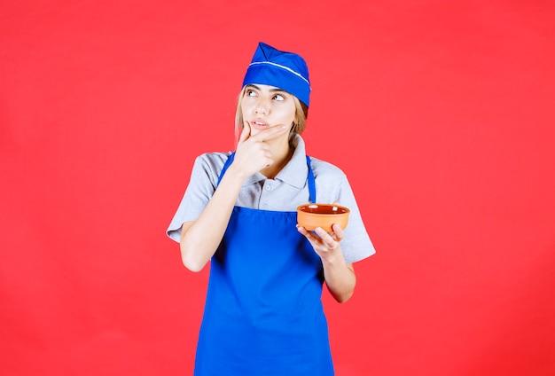 Женщина-повар в синем фартуке держит чашку с лапшой и выглядит сбитой с толку и думает о том, как сделать ее вкуснее