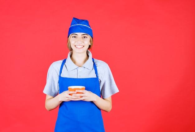 Женщина-шеф-повар в синем фартуке держит чашку с лапшой