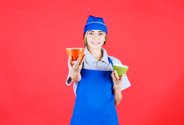 Женщина-повар в синем фартуке держит оранжевые и зеленые керамические чашки с лапшой и делится одной со своим партнером