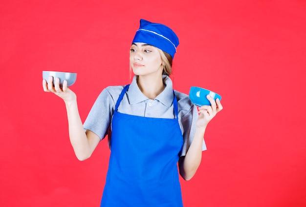 Женщина-повар в синем фартуке держит две керамические чашки с лапшой и не понимает, что делает выбор