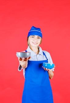 Женщина-шеф-повар в синем фартуке держит две керамические чашки с лапшой и делится одной с клиентом