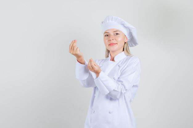 お金のジェスチャーと笑顔をしている白い制服を着た女性シェフ