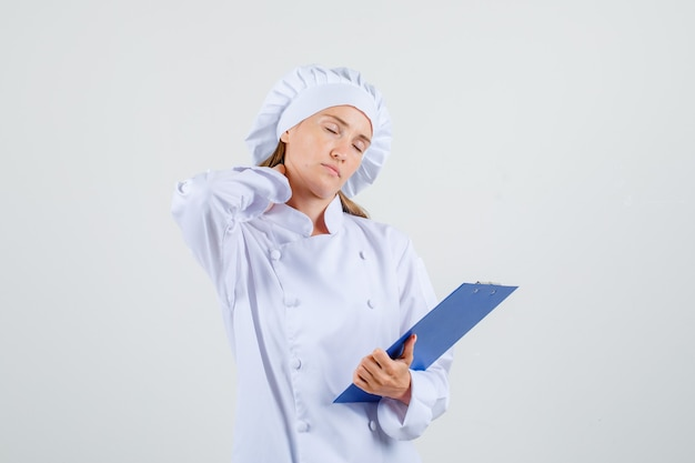 首に手でクリップボードを保持し、疲れているように見える白い制服を着た女性シェフ