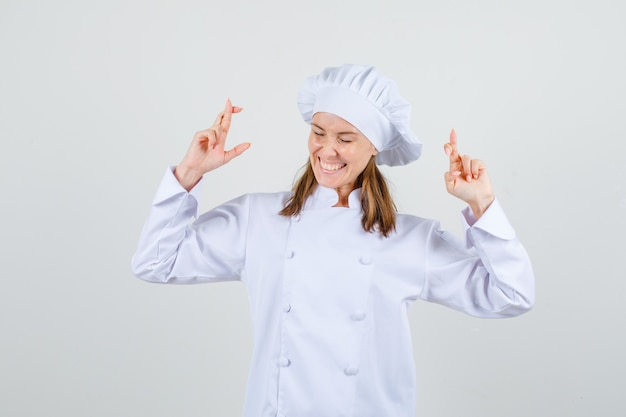 指を交差させて幸せそうに見える白い制服を着た女性シェフ
