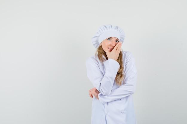 口に手を握って繊細な白い制服を着た女性シェフ