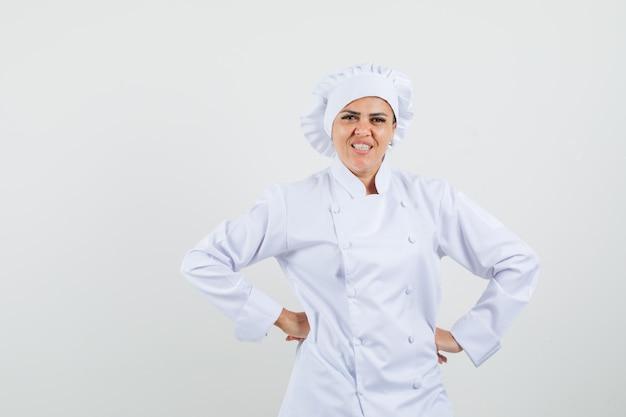 腰に手をつないで陽気に見える白い制服を着た女性シェフ