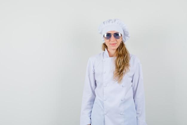 カメラ目線と笑顔の白い制服を着た女性シェフ