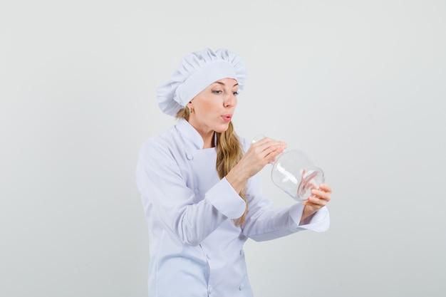 Женщина-повар в белой униформе смотрит в химическую фляжку и с любопытством смотрит