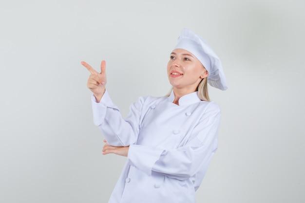 銃のジェスチャーを示し、陽気に見える白い制服を着た女性シェフ