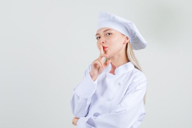 Женщина-шеф-повар в белой форме показывает жест молчания и улыбается