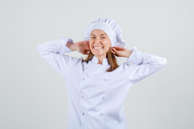 Женщина-повар в белой форме протягивает руки вокруг головы и выглядит радостным