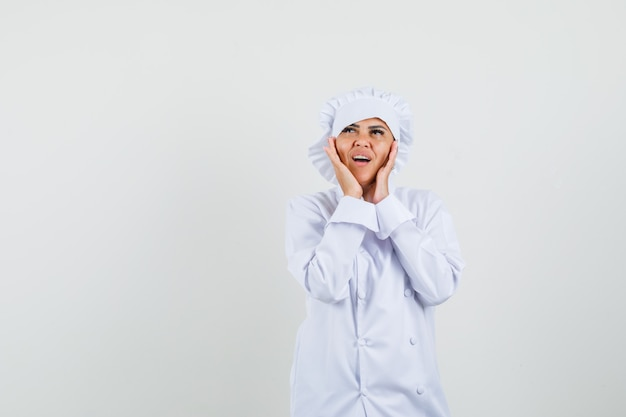 手で頬に触れて物思いにふける白い制服を着た女性シェフ
