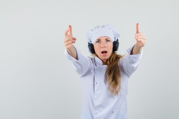 Female chef inviting to come while wearing headphones in white uniform