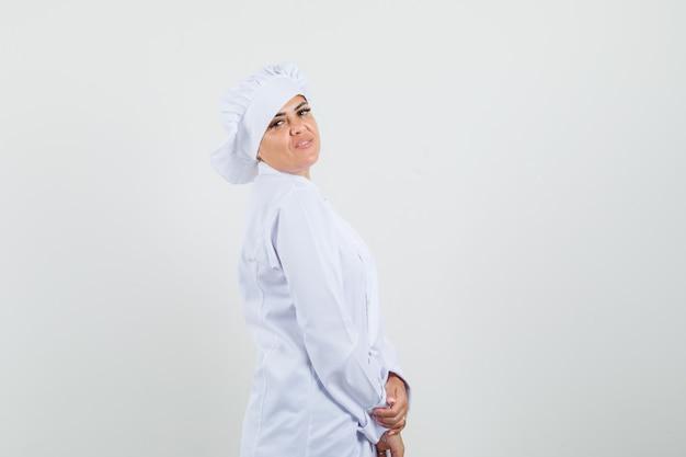 흰색 제복을 입은 카메라를보고 쾌활한 찾고 여성 요리사.