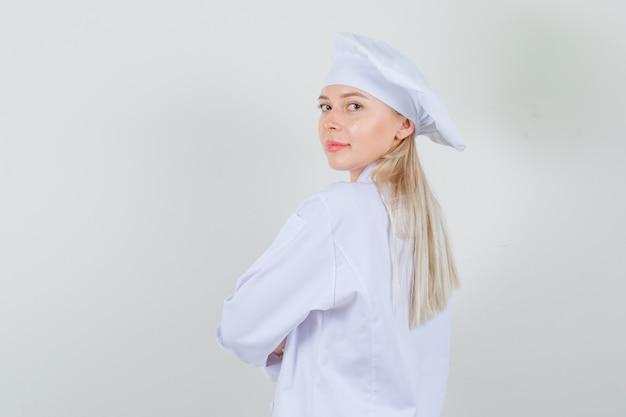 白い制服を着て肩越しにカメラを見て、ポジティブに見える女性シェフ。