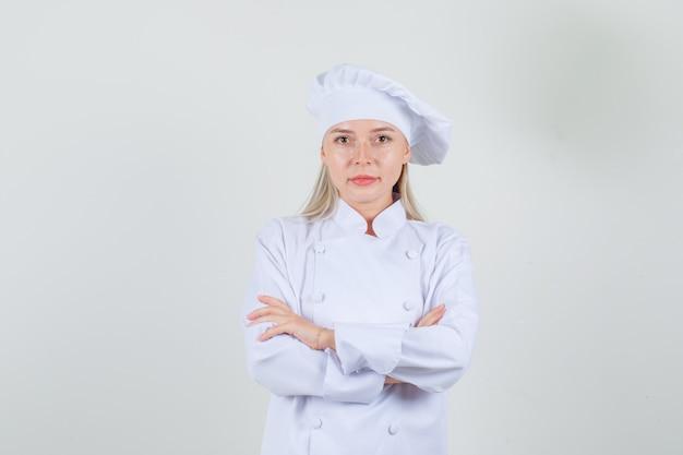 白い制服を着た腕を組んでカメラを見て、ポジティブに見える女性シェフ