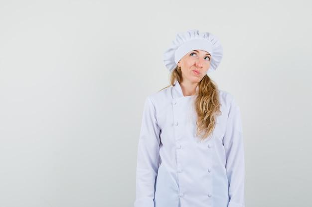 Женщина-повар смотрит вверх, нахмурившись, в белой форме и выглядит нерешительно.