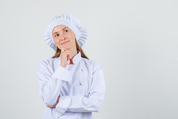 Cuoco unico femminile che osserva in su con la mano sul mento in uniforme bianca e che sembra promettente. vista frontale.