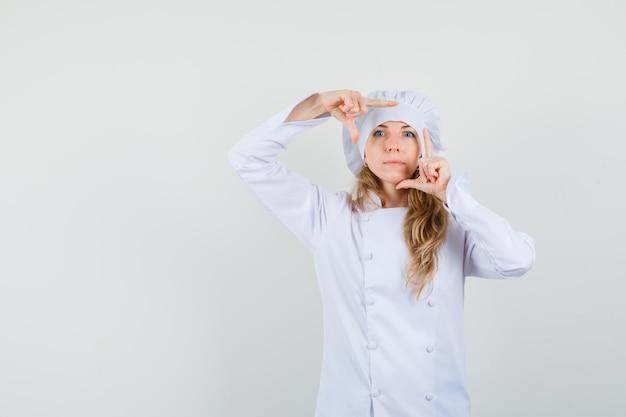 白い制服を着た女性シェフがフレームジェスチャーを作る