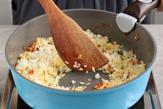 Женщина-повар готовит жареный рис на сковороде, шаг за шагом на кухне
