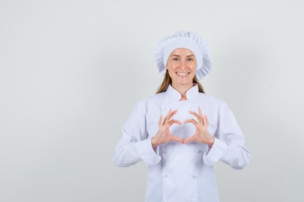 Cuoco unico femminile che fa figura del cuore in uniforme bianca e che sembra felice