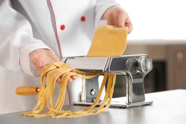 Женский шеф-повар делает лапшу с макаронной машиной за столом