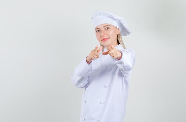 白い制服を着た銃のジェスチャーでカメラを指して陽気に見える女性シェフ