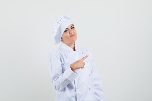 白い制服を着て背を向け、自信を持って見える女性シェフ。