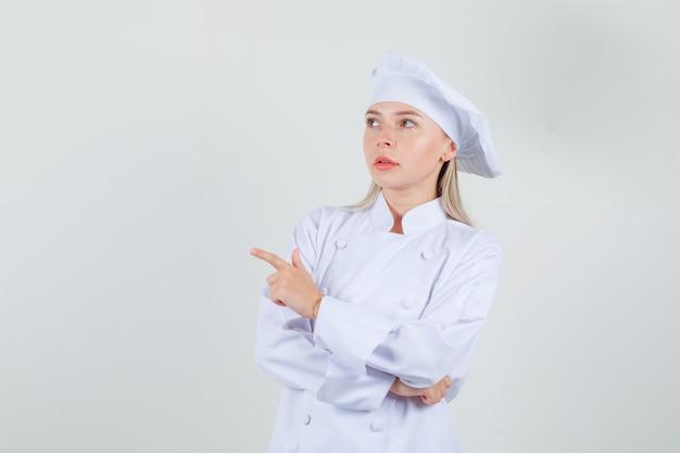 白い制服を着て目をそらし、思慮深く見える女性シェフ。正面図。
