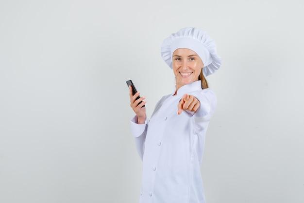 白い制服を着たスマートフォンでカメラに指を指し、陽気に見える女性シェフ。正面図。